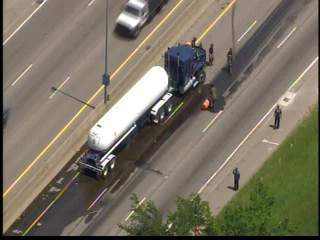 Car wedged under tanker truck