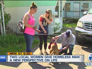 Two women help homeless man and his dog