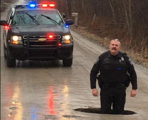 Officer stands knee-deep in massive pothole
