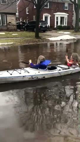Kids in Grosse Pointe Woods canoe down a flooded street